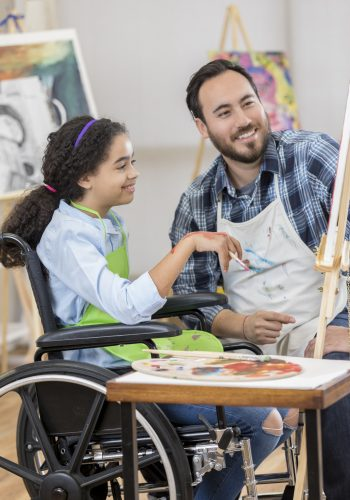 Confident preteen African American art student paints in an art studio. A male Hispanic teacher is instructing her. She is holding a paintbrush. A palette is on the table.