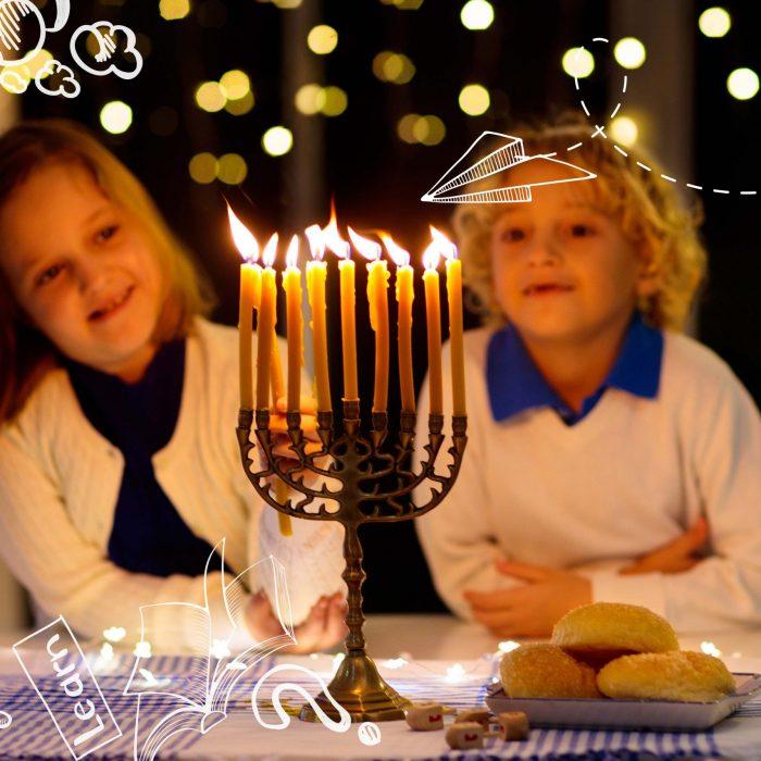 Jewish holiday Hanukkah background with vintage menorah and spinning top dreidel over lights bokeh.